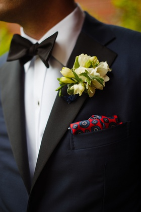 Groom in tuxedo bow tie white cluster boutonniere and red blue pocket square