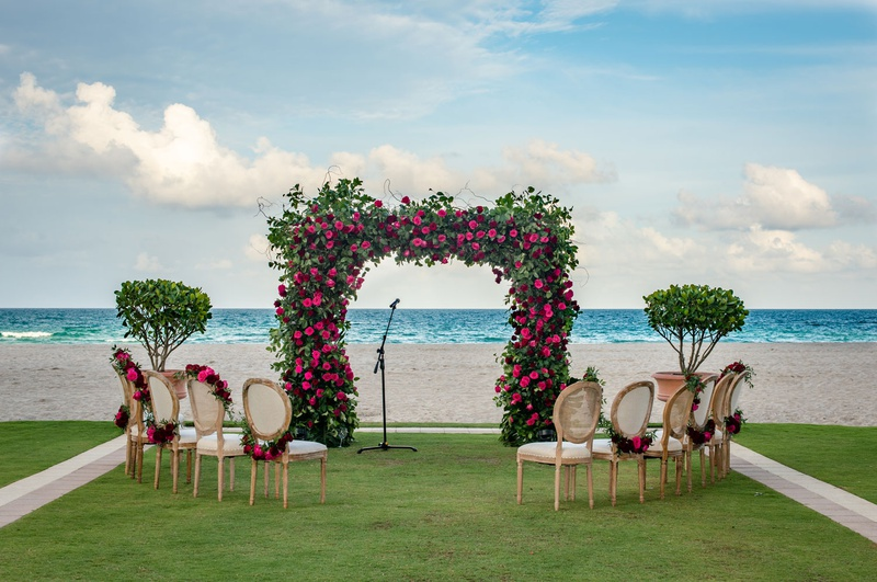 wedding ceremony at acqualina resort and spa in florida greenery arch pink flowers chairs garlands