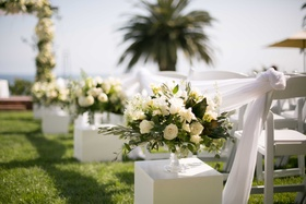 small floral arrangements lining aisle white green roses on white stands outdoors grass wedding