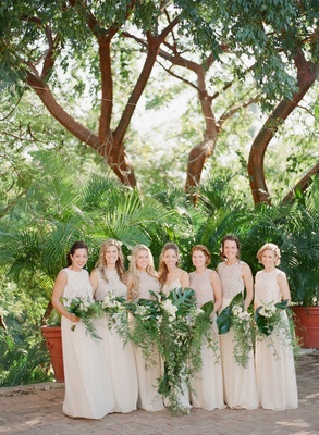 Bride and bridesmaids in white ivory cream holding green cascading bouquets greenery leaves palm