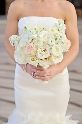 bride holds a bouquet of blush and ivory roses and other small flowers