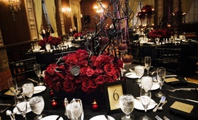 Wedding reception table with a red rose and manzanita branch centerpiece