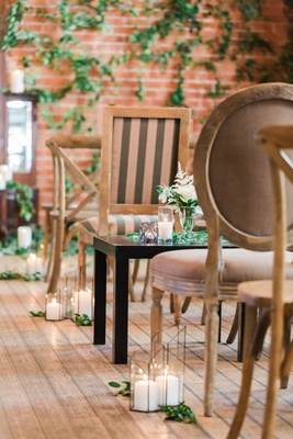 Wedding ceremony wood floors brick wall with greenery wood chairs candles greens