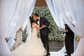 Bride in off shoulder wedding dress kisses groom at wedding under draped chuppah white flowers