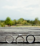 Engagement ring and bands in between wood planks