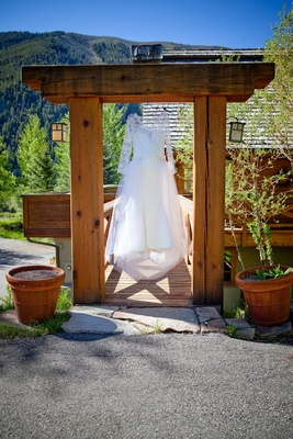 Long sleeve wedding dress hanging from mountain lodge