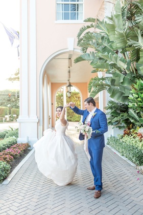 The Confused Millennial wedding shoot bride and groom dancing at venue outside pink hotel palm trees
