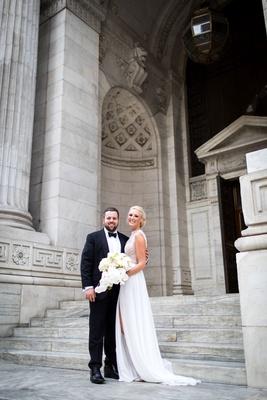 Bride in Julie Vino wedding dress front high slit sleeveless groom in tuxedo in front of new york