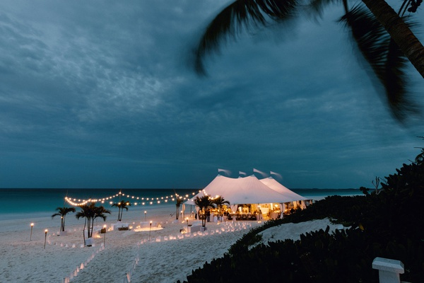 wedding reception under tent on beach destination wedding harbour island bahamas sunset lantern