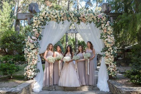 bridesmaids in halter bridesmaid dresses champagne taupe gowns ceremony flower arch bouquets ribbons