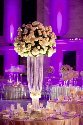 Tall rose and hydrangea wedding flower arrangement on top of Swarovski crystal stand at reception