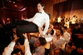 Male wedding guests lifting groom up over dance floor