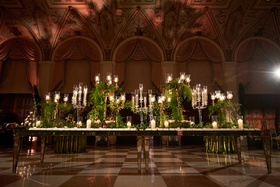 escort card table with lots of candelabra and lots of greenery