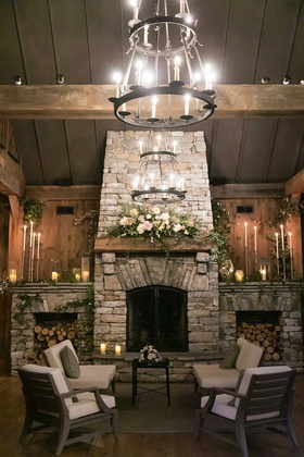wedding reception lounge wood stacked fireplace mantle with pink white flowers greenery chandeliers