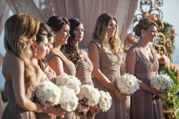 Bridesmaids holding white nosegays in brown gowns
