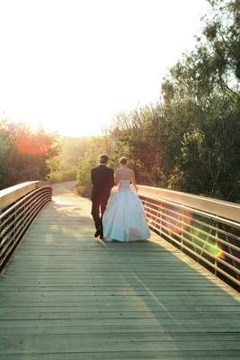 Newlyweds walking on bridge