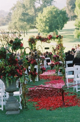 Rose petals on grass aisle flanked by greenery