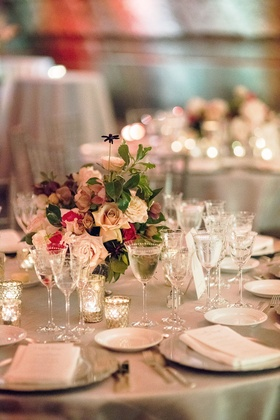 Round table with crystal glassware, candle votives, low flower arrangement pink roses green leaves
