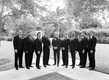 Black and white photo of groom in custom tuxedo with groomsmen in suits palm beach florida