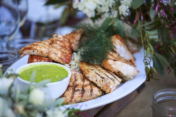 Rustic outdoor wedding reception table with platter of grilled salmon, risotto, green sauce, dill