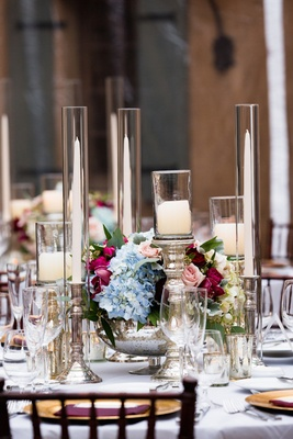 Taper candles and pillar candles on mercury glass stands with multicolored centerpiece