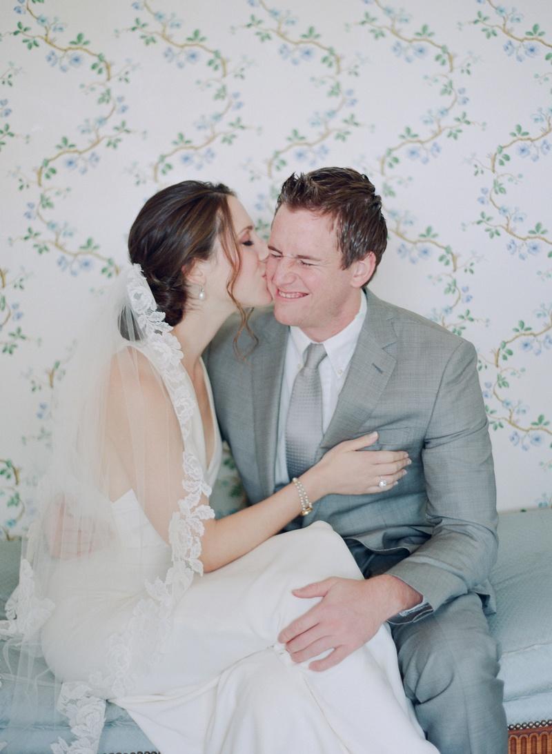 Bride kissing groom's cheek in wedding dress