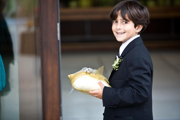 ring bearer holds yellow pillow with rings