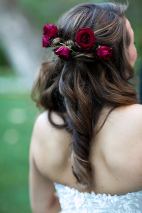 Bride in strapless wedding dress with curled brunette locks and deep burgundy roses in hairstyle