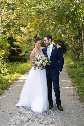 wedding portrait bride in strapless wedding dress high bun bouquet groom in suit with light green ti