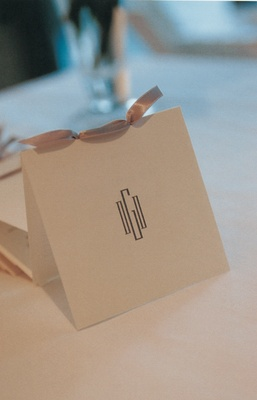 Invitation decorated with couple's initials and a gray ribbon