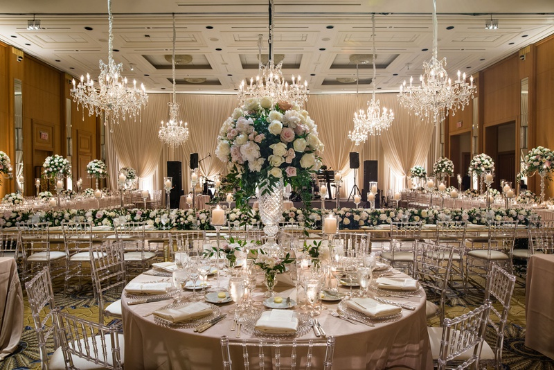 wedding reception hotel ballroom round table tall centerpiece clear chairs head table chandeliers