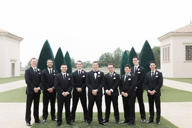 groom and groomsmen in black tuxedos with ties groom in bow tie white flower boutonniere