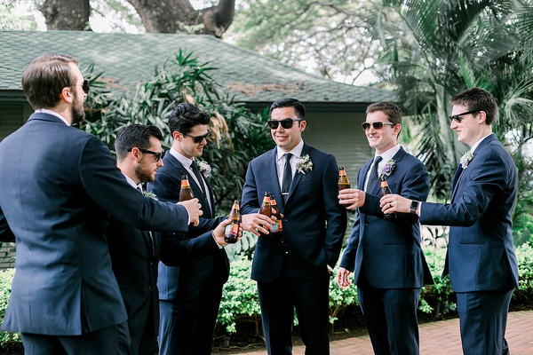 groom and groomsmen in suits and sunglasses with bottles of beer hawaii wedding preparation