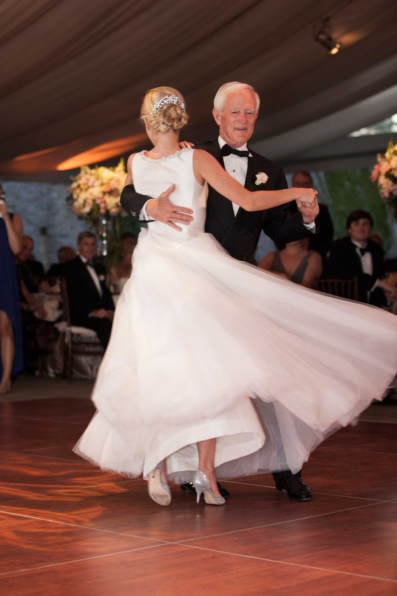 a bride twirls in her full tulle skirt during the father daughter dance at her reception