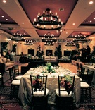 amber ballroom with white tables and red and green floral centerpieces