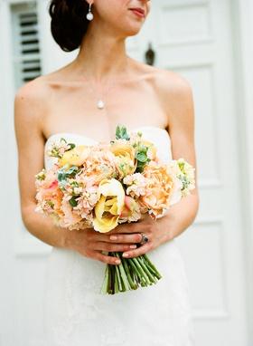 spring wedding ideas bright peach yellow pink orange wedding bouquet bride holding stems greenery