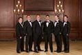 Groom and groomsmen in black and white tuxedos with bow ties