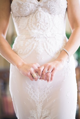 Bride in strapless beaded gown with engagement ring, bracelet, and matching ring to bridesmaids