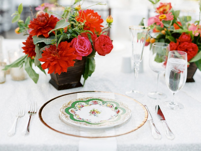 Green colorful china plate on top of clear gold rim charger at outdoor wedding