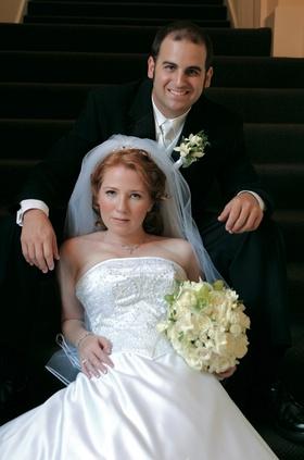 Bride leans against groom on flight of stairs