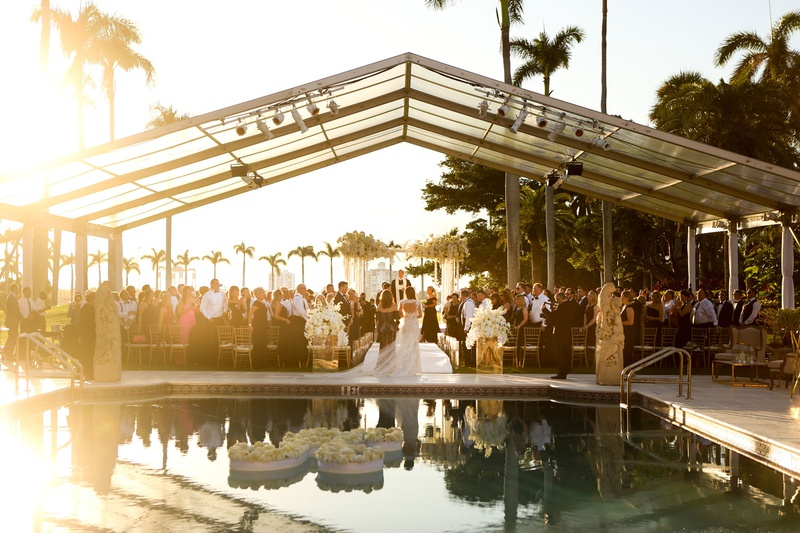 wedding processional with mother and bride pool with floating letter k flower clear top tent sunset