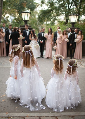 four flower girls in white dresses with butterfly designs flower crowns ribbons long sleeve lace