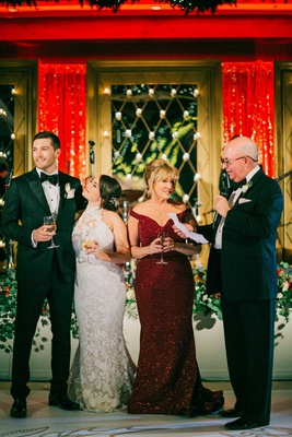 bride and groom with mother of bride in sparkling red sequin gown father of groom toasts holiday