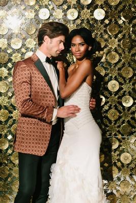 bride in inbal dror mermaid gown, groom in bronze patterned tuxedo jacket, golden wall as backdrop