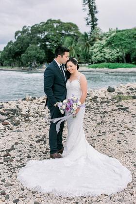 bride and groom on island of maui in hawaii destination wedding couple portrait purple flowers