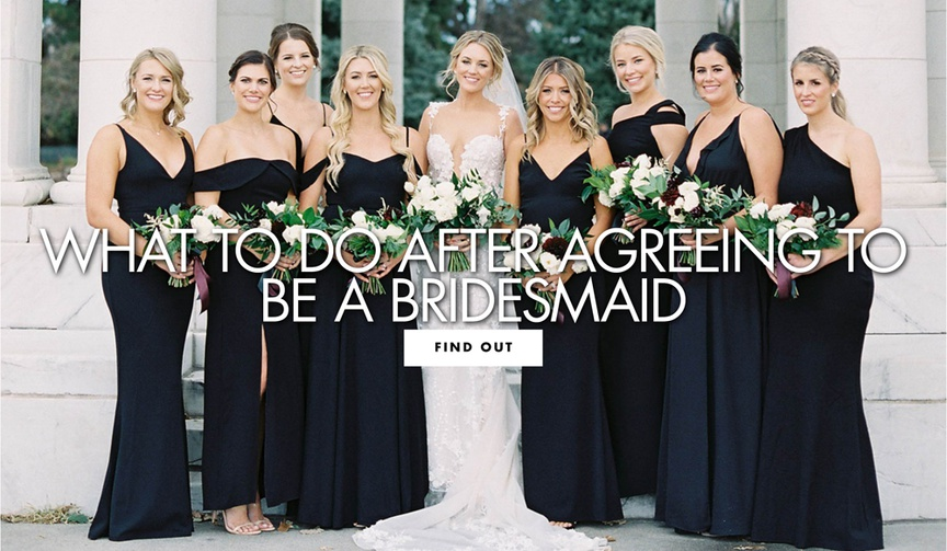 group of bridesmaids in mismatched navy dresses with bride in lace gown