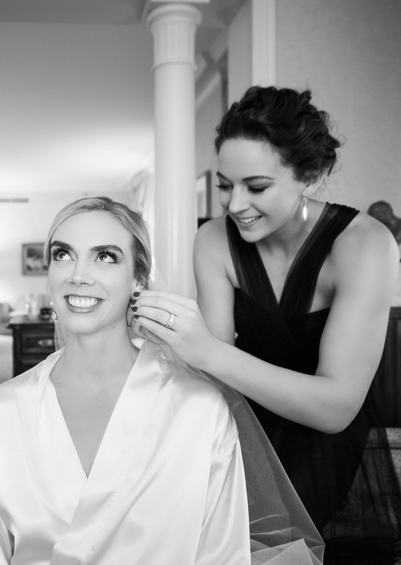 maid of honor helps bride with earrings