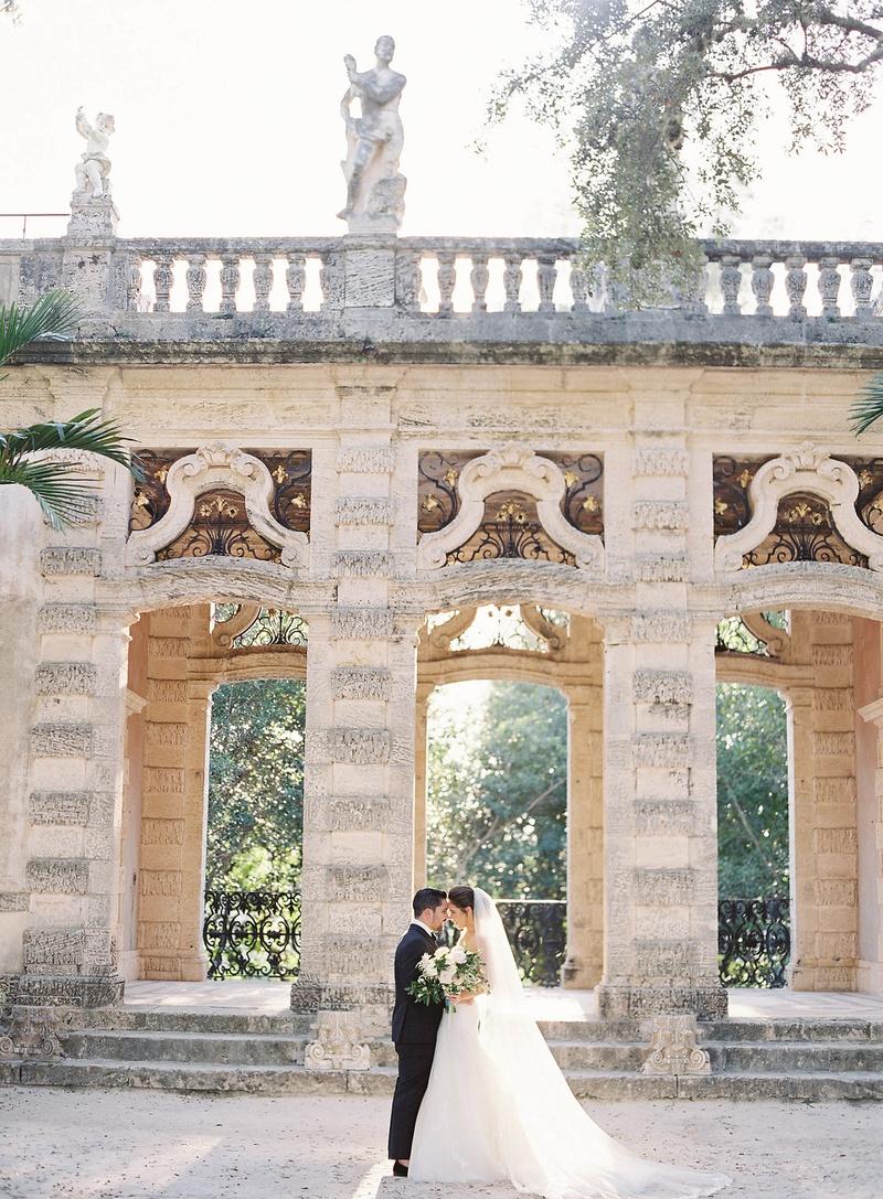 Bride in wedding dress groom in tuxedo in front of villa grounds Vizcaya Museum and Gardens in Miami
