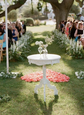 Shabby chic white altar table in front of flower petal heart