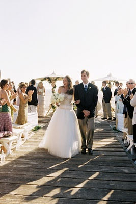 Bride and groom walk up wood plank aisle on beach